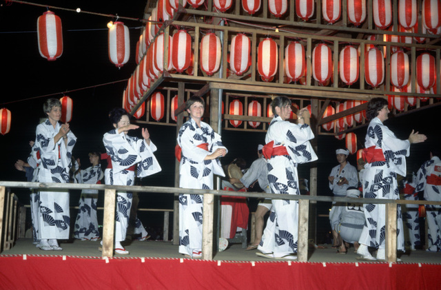 Navy wives join with Japanese dancers participating in the annual community folk dancing ceremony known as Bon Odori. The dancing is one feature of the Obon services, which are similar to a Western-style All Soul's Day observance or Halloween. All Hands - May 1983