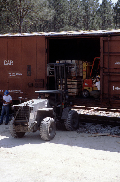 Pallets are removed from a railroad car with the use of a Case M4K rough terrain forklift truck during LIFELINE Operations. The operations are being conducted by the 155th, 567th and 870th Transportation companies