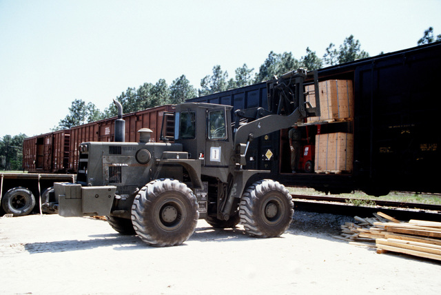 Pallets are unloaded from a railroad car by an IHC M10A forklift during LIFELINE Operations. The operations are being conducted by the 155th, 567th and 870th Transportation companies