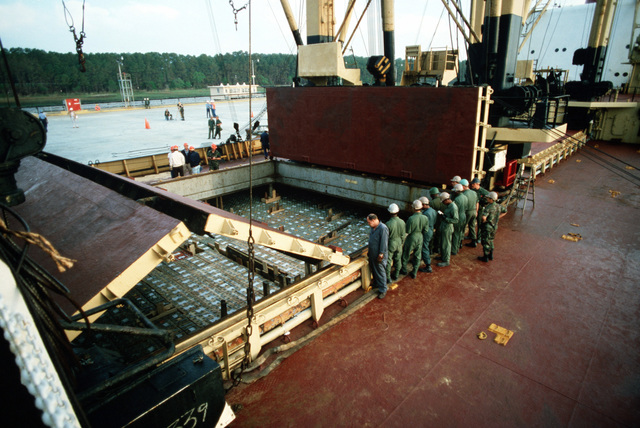 The hatches of the chartered Military Sealift Command cargo ship BUILDER (T-AK 2031) are opened for unloading during LIFELINE Operations. The operations are being conducted by the 155th, 567th and 870th Transportation companies