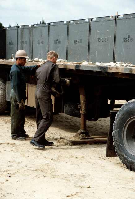 The landing legs of an M872 trailer are adjusted prior to loading during LIFELINE Operations. The operations are being conducted by the 155th, 567th and 870th Transportation companies