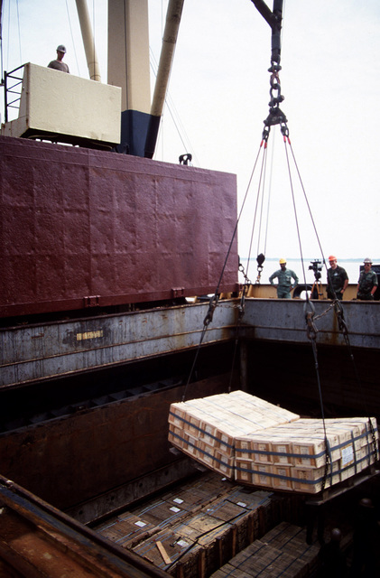Two pallets of ammunition are unloaded from the hold of the chartered Military Sealift Command cargo ship BUILDER (T-AK 2031) during LIFELINE Operations. The operations are being conducted by the 155th, 567th and 870th Transportation companies