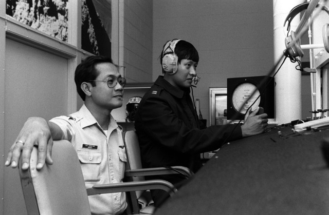 Captain Franciscus Soeratimo (left) of Indonesia and Captain Vatit Sakdisubha of Thailand, both undergoing certification training as physiology instructors, monitor oxygen chamber training at the Wilford Hall USAF Medical Center