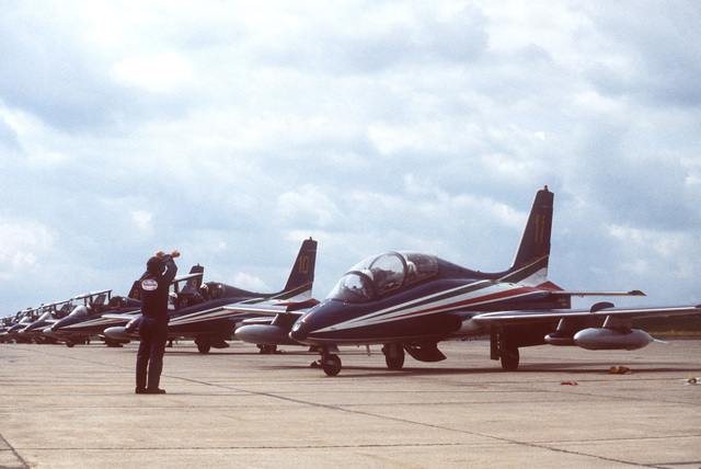 A member of the 50th Field Maintenance Squadron lines up the Italian Air Force Frecce Tricolori aerobic team's Aermacchi M. B. 339PAN aircraft for refueling