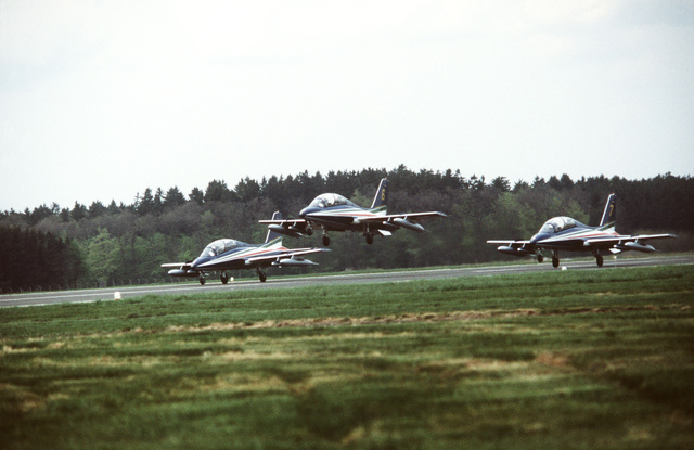 Three Aermacchi M.B. 339PAN aircraft, from the Italian Air Force Frecce Tricolori aerobic team, touch down on the runway in a wedge formation during a demonstration