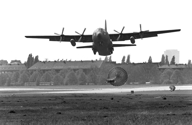 A C-130 Hercules aircraft drops a pallet of equipment on the flight line during a demonstration of the low-altitude parachute extraction system (LAPES) at the Tempelhof Central Airport Open House '83