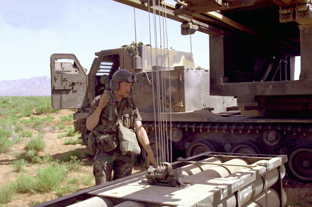 A member of the 3rd Bn., 6th Field Arty., 1ST Infantry Div., prepares a hoist for loading Multiple Launch Rocket System (MLRS) pods into a Self-Propelled Loader Launcher (SPLL) during a live fire exercise