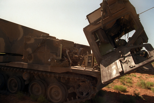 The cab hatch and engine compartment are open on a Self-Propelled Loader Launcher (SPLL) as members of the 3rd Battalion, 6th Field Artillery, 1ST Infantry Division, prepare it for a live fire exercise
