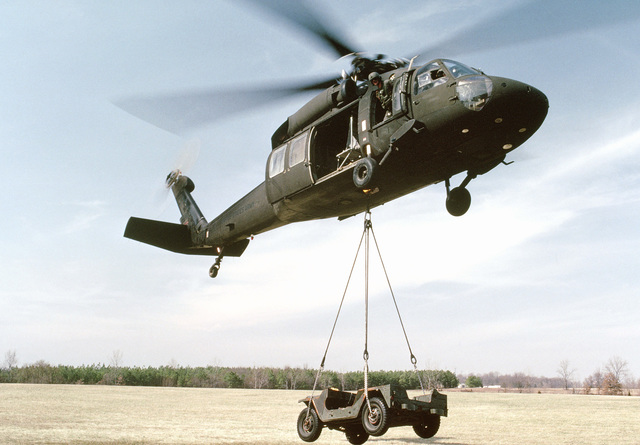 A UH-60 Blackhawk helicopter lifts an M151 jeep utility vehicle during training at the Army Air Assault School