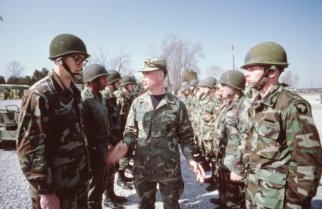 An instructor walks between two ranks of infantrymen asking questions to test their mental alertness at the Army Air Assault School