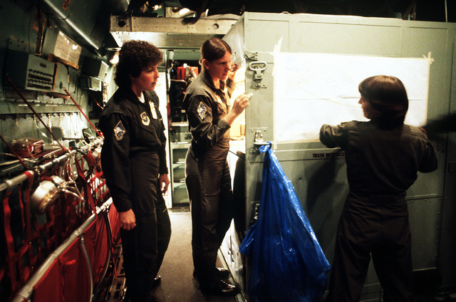 First LT. Terri Ollinger, co-pilot, assembles a map in the passenger section of a C-141 MEDEVAC aircraft as crew members SGT. Mary Eiche, left, and TECH. SGT. Donna Wertz look on. The women are part of the first Air Force all-female flight crew to fly an overseas mission. The women will fly a C-141 MEDEVAC aircraft to Rhein-Main Air Base, West Germany, with a stop-over at Lajes Field, Azores