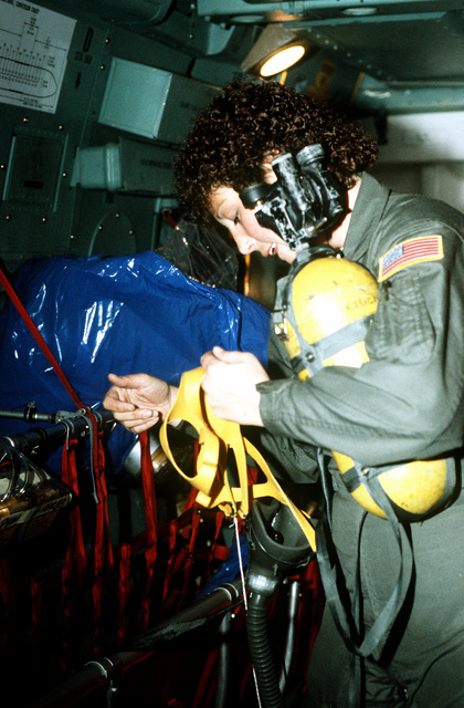 SGT. Mary Eiche, load master, checks the operation of oxygen masks aboard a C-141 MEDEVAC aircraft prior to takeoff. She is part of the first Air Force all-female flight crew to fly an overseas mission. The women will fly the C-141 to Rhein-Main Air Base, West Germany with a stop-over at Lajes Field, Azores