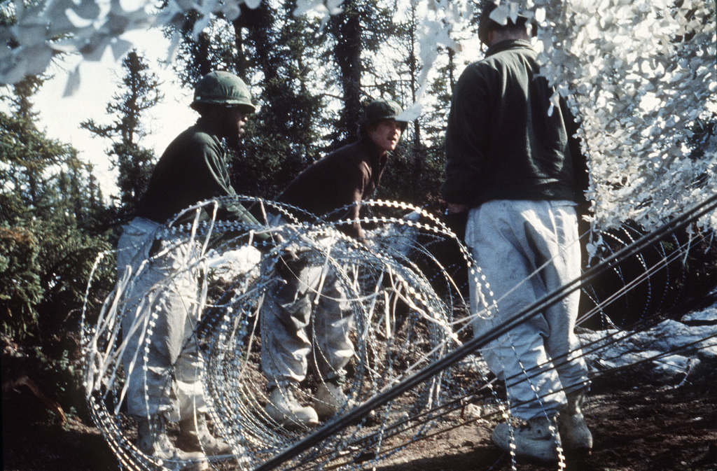 Members of the 327th Infantry Regiment set up concertina wire around an ammunition tent during CELESTIAL EMPIRE '83
