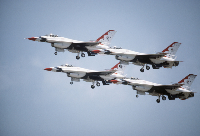 A left side view of four F-16 Fighting Falcon aircraft assigned to the Thunderbirds flight demonstration team in flight with their landing gear down during the Open House Air Show