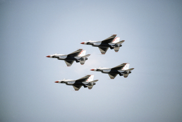 A left underside view of four F-16 Fighting Falcon aircraft assigned to the Thunderbirds flight demonstration team, in flight in a normal diamond formation during the Open House Air Show