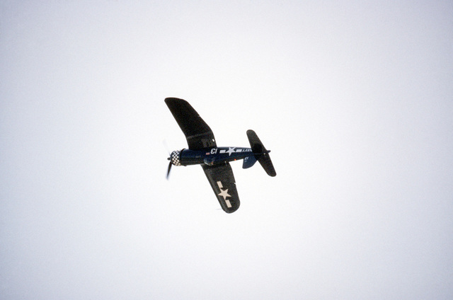 A Navy vintage F4U Corsair aircraft is used to perform an aerial stunt during the Open House Air Show