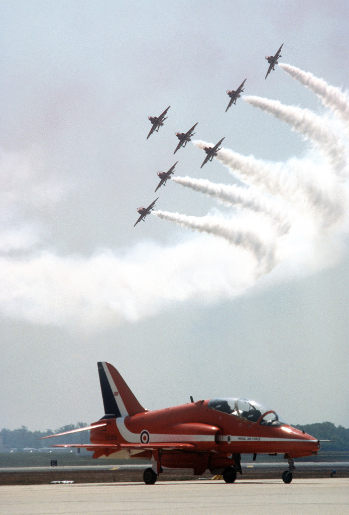 A Royal Air Force (British) BAe Hawk aircraft assigned to the Royal Air Force Red Arrows flight demonstration team is parked on the apron, while seven other Hawk aircraft are in flight overhead during the Open House Air Show