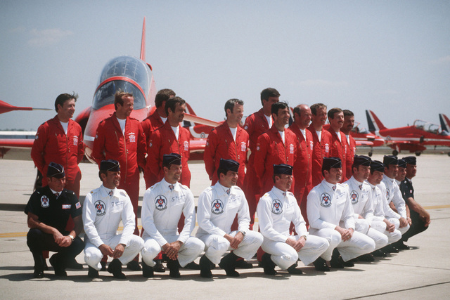 The Royal Air Force Red Arrows flight demonstration team (standing) and the US Air Force Thunderbirds, pose for photographers at the Open House Air Show. Behind them is the British BAe Hawk aircraft that the Red Arrows fly