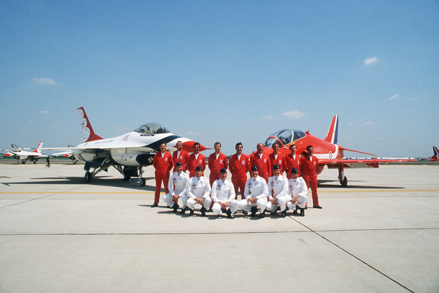 The Royal Air Force Red Arrows flight demonstration team (standing) and the US Air Force Thunderbirds Flight Demonstration Team, pose for photographers at the Open House Air Show. Behind them is the British BAe Hawk aircraft, right, and an F-16 Fighting Falcon aircraft