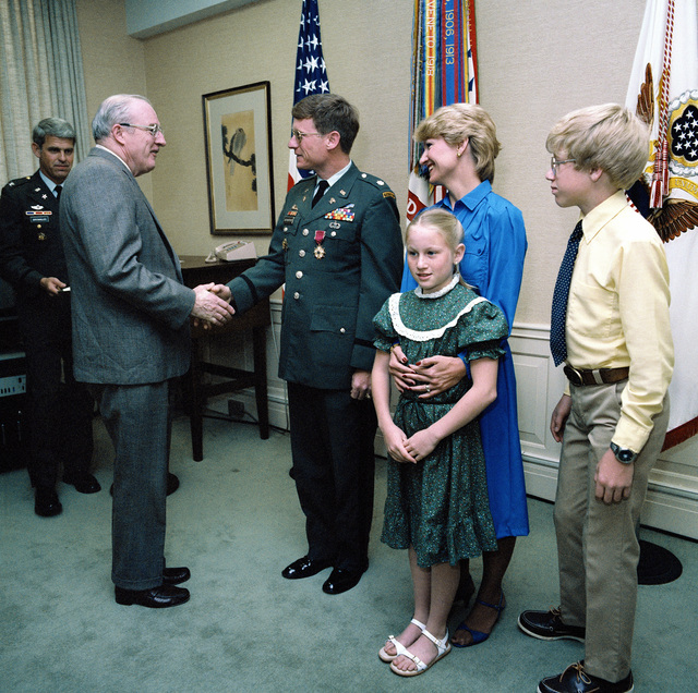 Undersecretary of the Army James R. Ambrose presents the Legion of Merit to LCOL Wilson R. Rutherford, during the ceremony at the Pentagon. Attending the ceremony are LCOL Rutherford's wife, Carolyn, his daughter Megan and his son Troy