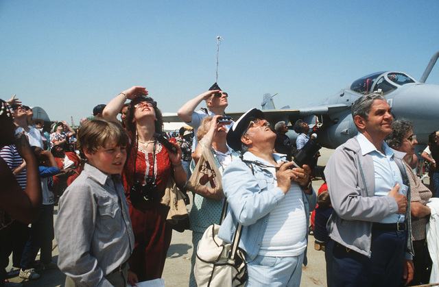 Visitors at the Open House Air Show look up to watch an aerial demonstration. Behind them is an A-6 Intruder aircraft on display