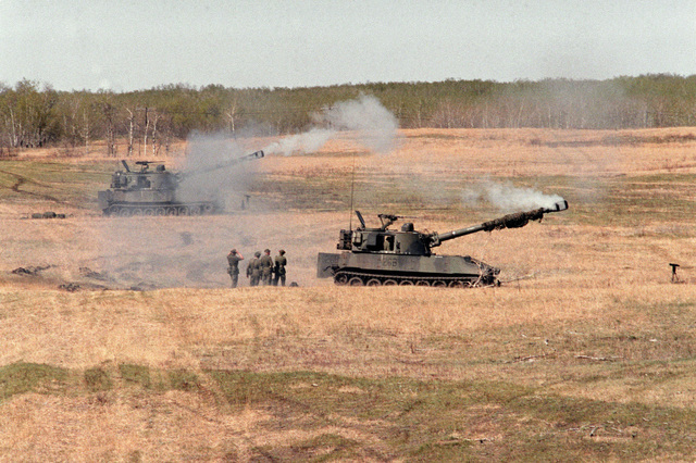 A pair of a Canadian army M-109A1 155 mm self-propelled howitzers is used to conduct a firing mission during the combined United States/Canadian NATO exercise RENDEZVOUS '83