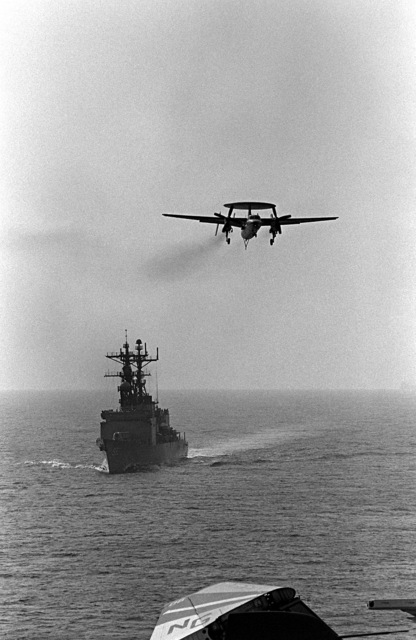 An E-2C Hawkeye airborne early warning aircraft makes a final approach for the flight deck of the aircraft carrier USS RANGER (CV-61). The Spruance class destroyer USS FLETCHER (DD-992) is underway in the background