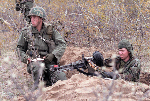 Members of Company B, 3rd Battalion, 327th Infantry, 101st Airborne Division, set up an M60 machine gun in a foxhole during the combined United States/Canadian NATO exercise RENDEZVOUS '83