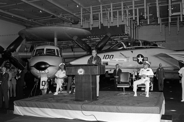 Vice President George Bush addresses the guests and crewmen attending a ceremony on the hangar deck during his visit aboard the aircraft carrier USS RANGER (CV-61). Directly behind him are an E-2 Hawkeye airborne early warning aircraft and an F-14 Tomcat aircraft