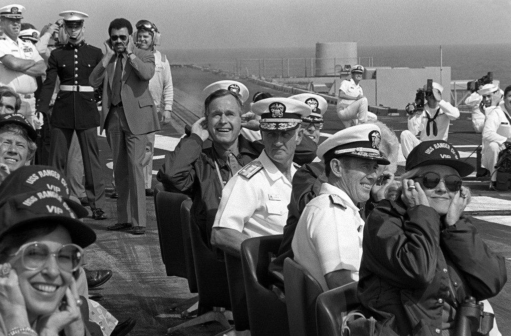 Vice President George Bush watches an airshow from the flight deck of the aircraft carrier USS RANGER (CV-61) during his visit to the ship