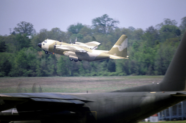 Left side view of a C-130 Hercules aircraft painted in desert camouflage, taking-off. Another Hercules (foreground), with a European paint scheme, prepares for take-off