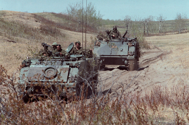 A pair of Canadian army M-113A1 armored personnel carriers brings up the rear of a convoy during the combined United States/Canadian NATO exercise RENDEZVOUS '83