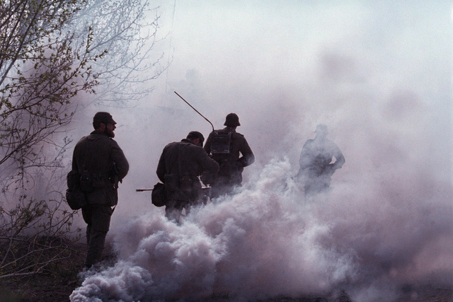 A smoke grenade obscures Canadian army infantry troops as they move forward during a mock battle taking place during the combined United States/Canadian NATO exercise RENDEZVOUS '83