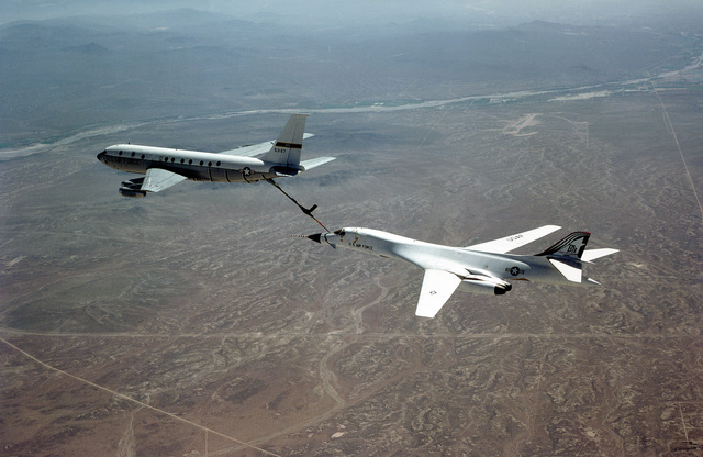 An air-to-air left rear view of a B-1B bomber aircraft being refueled in flight by a KC-135 Stratotanker aircraft
