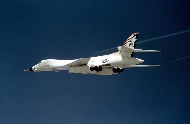 An air-to-air left rear view of a B-1B bomber aircraft with contrails streaming from its wingtips