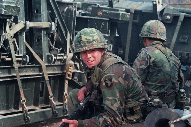 Members of the 3rd Battalion, 327th Infantry, 101st Airborne Division, take cover behind pallets of heavy equipment during a mock attack by members of the Canadian Army. They are participating in the combined United States/Canadian NATO exercise RENDEZVOUS `83