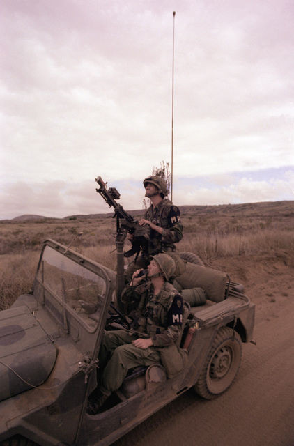 """PFC. Terry Ostrander and SGT. Curtis Vanchoff of the 25th Inf. Div. Military Police, spot """"enemy"""" aircraft flying overhead and prepare to fire on them with an M-60 machine gun during annual training exercises"""