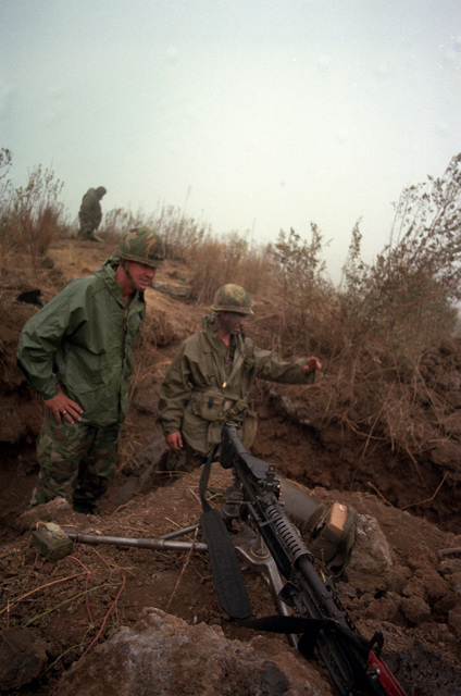 Major General William H. Schneider, commander of the 25th Infantry Division, examines the M-60 machine gun pit of PFC Thomas Flood, assistant gunner with Company A, 1ST Battalion , 35th Infantry, 25th Infantry Division. Thomas' unit is undergoing an annual Army Training and Evaluation Program at the US Army`s Pohakuloa Training Area