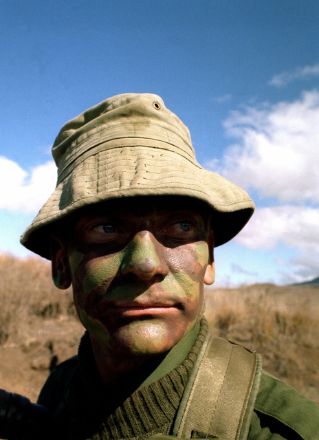 """Major Peter Maher, Commander, Company C, Royal Australian Regiment and commander of the opposing forces against the 35th Infantry, 25th Infantry Division, looks advancing """"enemy"""" troops during training exercises"""