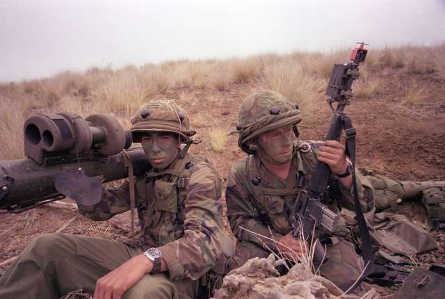 SPEC. 4 Michael Olague and PVT. Gregory Kent of the 1ST Bn., 35th Inf., 25th Inf. Div., armed with the Dragon missile anti-tank weapon system and MILES (Multiple Integrated Laser Engagement System), watch for opposing forces on Puu Maile during their annual training exercises