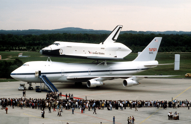 Spectators observe the arrival of the Space Shuttle Enterprise and its modified 747 transport aircraft at the Koln-Bonn Airport. The shuttle will be on display at the airport for five days before going on to the Paris Air Show