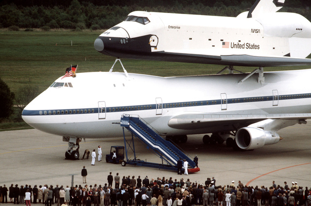 Spectators observe the arrival of the Space Shuttle orbiter and its specially-modified 747 transport aircraft at Koln-Bonn Airport. The Enterprise is at the airport for five days prior to going to the Paris Air Show