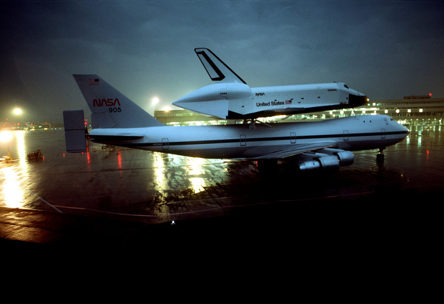 A night view of the Space Shuttle orbiter Enterprise and its specially-modified 747 transport aircraft at Koln-Bonn Airport. The Enterprise is at the airport for five days prior to the Paris Air Show