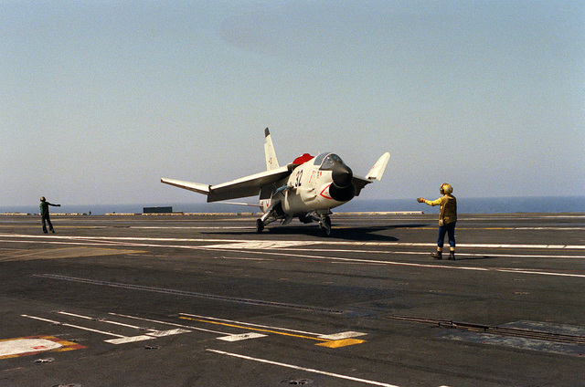 A plane director signals instructions to the pilot of a French Marine F-8E (FN) Crusader aircraft aboard the nuclear-powered aircraft carrier USS DWIGHT D. EISENHOWER (CVN-69)
