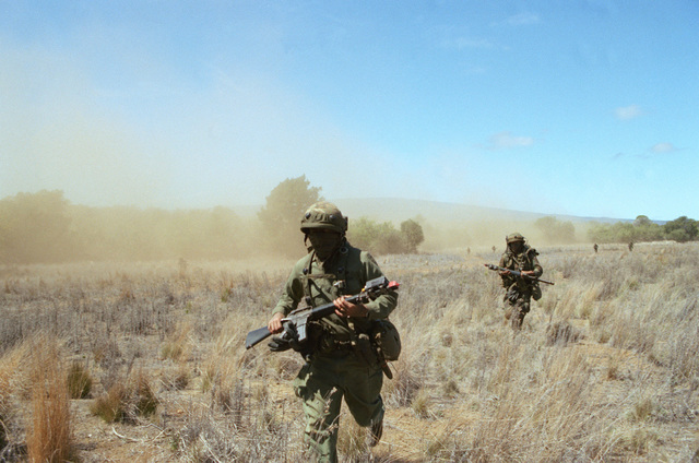 Members of Company C, 1ST Battalion, 35th Infantry, 25th Infantry Division, fan out after being dropped at a landing zone by helicopters from the 25th Comabt Aviation Battalion. They are conducting an airmobile assault against Australian Army units acting  as opposing forces for US troops undergoing their annual Army Training and Evaluation Program (ARTEP) at the Pohakuloa Training Area