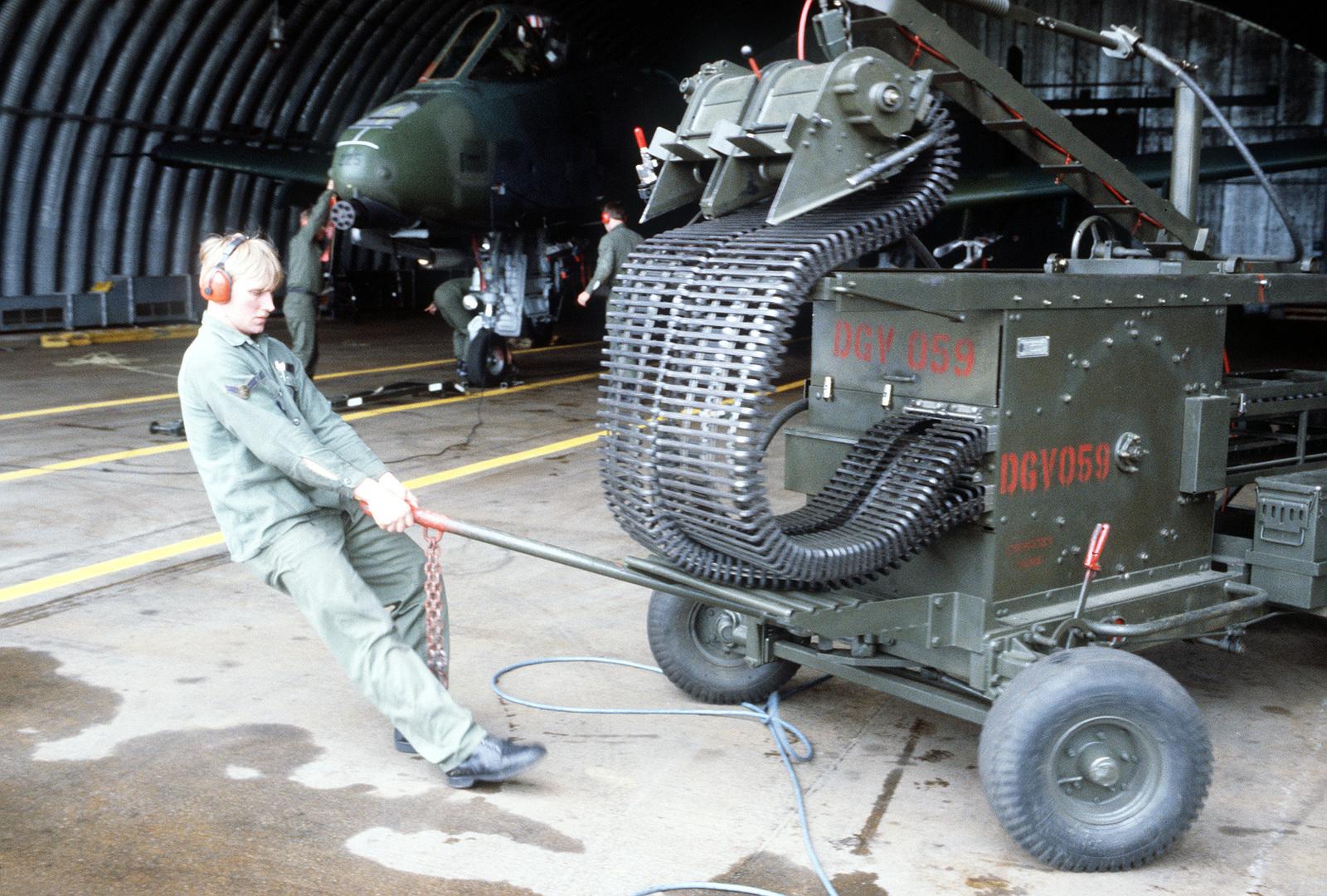 A munitions maintenance specialist pulls an ammunition