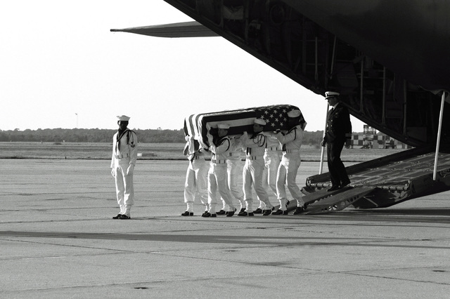 Six Navy pallbearers carry the flag-draped coffin of LT. CMDR. Albert A. Schaufelberger down the loading ramp of a transport aircraft. Schaufelberger was killed in San Salvador