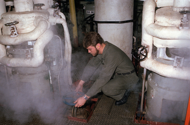 A boilerman technician opens the discharge valve to the main feed booster pump in the No. 4 main machinery room aboard the aircraft carrier USS KITTY HAWK (CV 63)