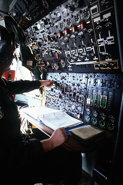 A flight engineer operates a panel of guages, switches and dials inside a C-141B Starlifter aircraft