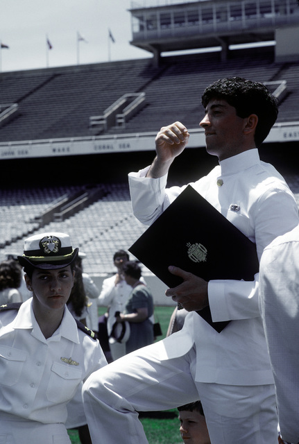A senior midshipmen at the U.S. Naval Academy holds his diploma following graduation ceremonies at the U.S. Navy-Marine Corps Memorial Stadium